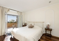 Master bedroom with bright white and wood interior