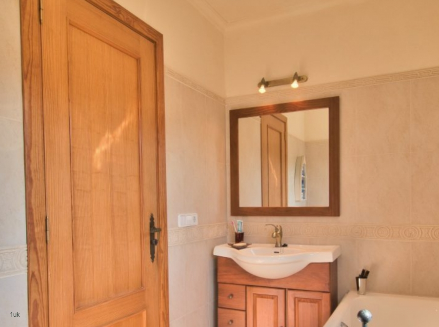 Bright cream and wooden look bathroom with sink and bathtub